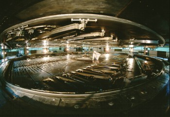 Inside the TRIUMF Cyclotron's vacuum tank. The top half of the cyclotron is raised four feet in order to gain access. This picture was taken with a fish-eye lens, but still gives a sense of the size and complexity of the accelerator components.