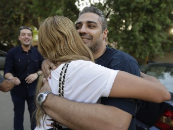 Mohamed Fahmy hugs his wife, Marwa Omara, after being released from Torah prison in Cairo, Egypt, on September 23, 2015. Fahmy and his colleague Baher, left, were among a group of 100 people pardoned by Egyptian President Abdel-Fattah el-Sissi on the eve of the major Muslim holiday of Eid al-Adha. (AP Photo/Amr Nabil)