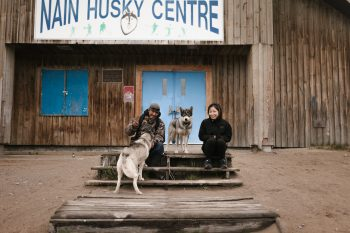 Husky pups with members of the Nain community. (Photo: Yanick Lesperance)