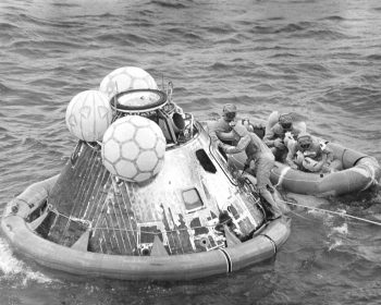 After splashdown in the Pacific Ocean, the Apollo 11 astronauts wait in the life raft as a pararescue man closes and secures the capsule hatch. The crew was then air lifted to the prime recovery ship, the USS Hornet, where they were housed in a Mobile Quarantine Facility (MQF). Image credit: NASA (Milt Putnam)